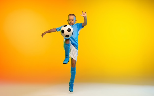 Run. young boy as a soccer or football player in sportwear practicing on gradient yellow studio