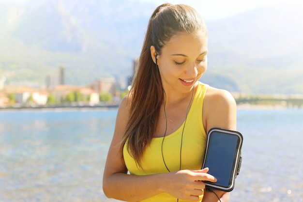 スマートフォンのアームバンドmp3プレーヤーからヘッドフォンで音楽を聴くランナーの運動選手。若い女性フィットネスジョギングトレーニングウェルネスコンセプト。