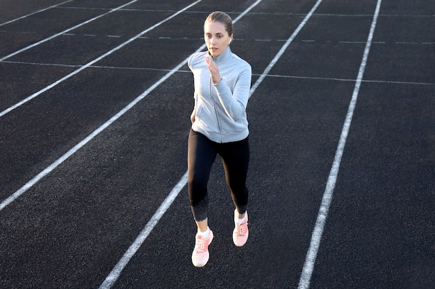 Runner athlete running on athletic track training her cardio in stadium. jogging at fast pace for competition.