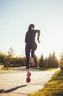 Бегущий спортсмен работает в парке. женщина фитнес бег трусцой тренировки оздоровительное понятие.