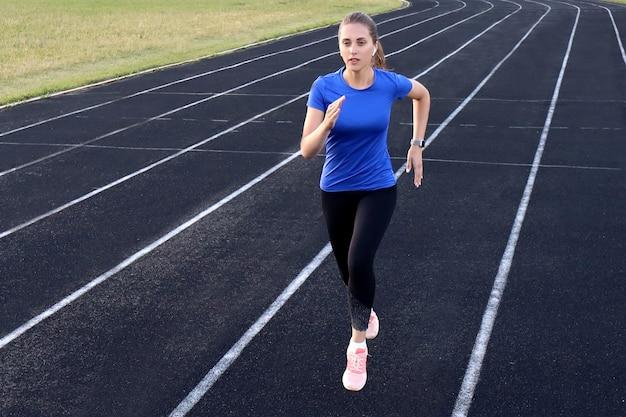 Спортсменка-бегун, бегущая по спортивной дорожке, тренирует кардио на стадионе. бег трусцой в быстром темпе для соревнований.