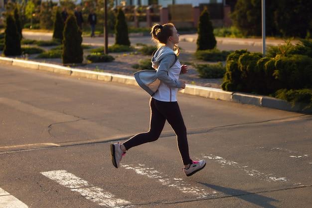 道路を走っているランナーの運動選手。女性フィットネスジョギングトレーニングウェルネスコンセプト。