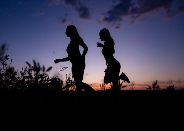 Бегущие спортсмены бегут на закате. закатные облака подсветка