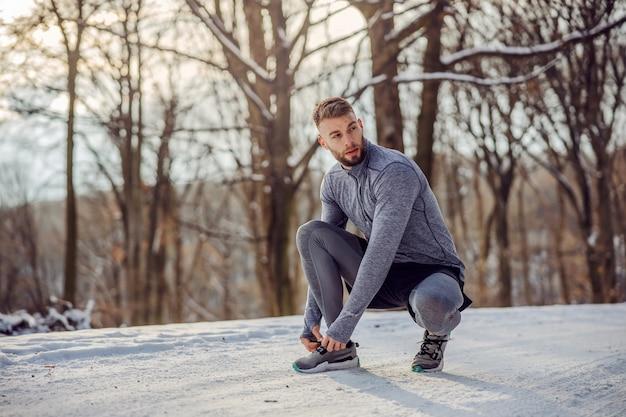 自然の中でトレイルにしゃがみ、雪の降る冬の日に靴ひもを結ぶランナー。
