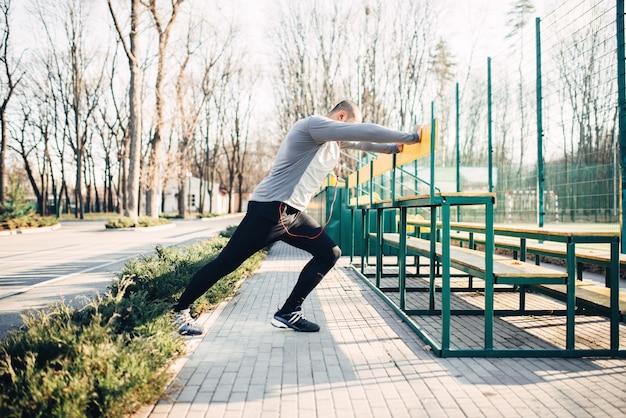 ジョギングの前にストレッチ運動をしているランナー。朝のフィットネストレーニングのジョガー。スポーツウェアのアスリート、屋外でのフィットネストレーニング