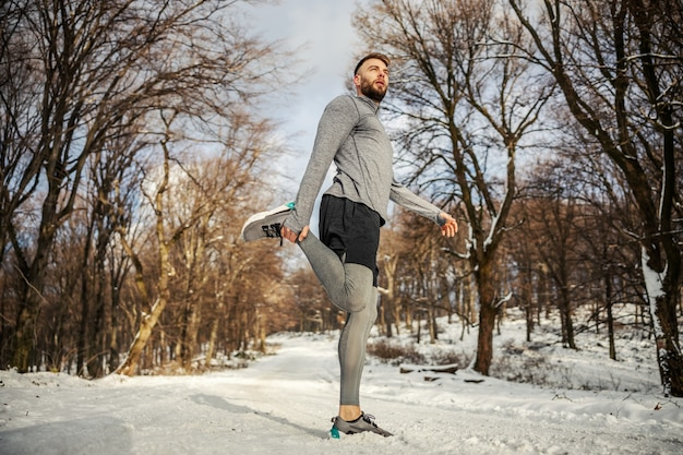 Бегун делает упражнения на разминку на природе в снежный зимний день. зимний спорт, снежная погода, упражнения на разминку