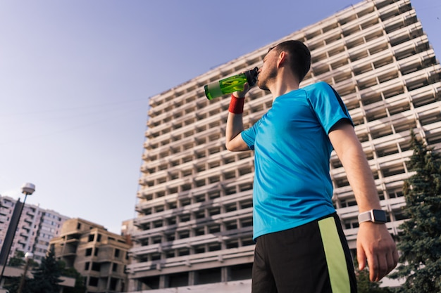 Runner drinking water during a break in the city