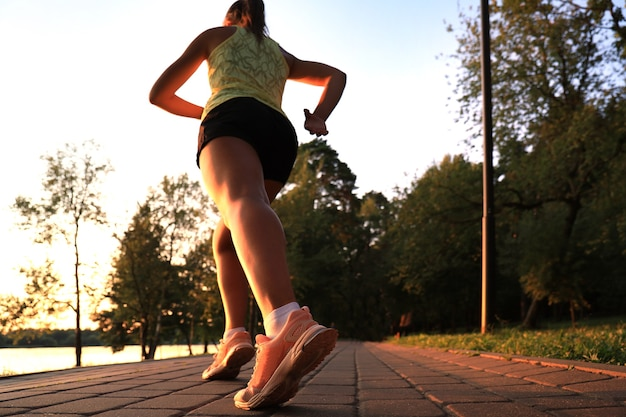 Ноги бегуна на крупном плане дороги на ботинке, открытом на закате или восходе солнца.