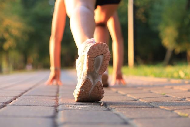 Runner feet running on road closeup on shoe, outdoor at sunset or sunrise.