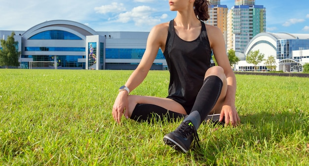 Runner girl resting on the football field. sports concept.