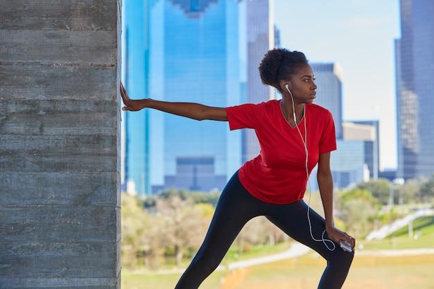 Runner girl stretching listening music earphones