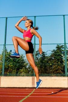 ジョギングコースでジャンプするランナー。走る前にウォームアップ運動をしている女性。