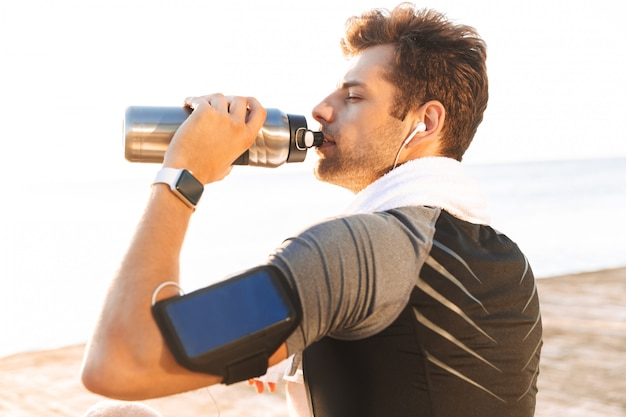 Runner man in tracksuit with smartphone arm holder sitting on wooden pier at seaside, and drinking water from thermos mug