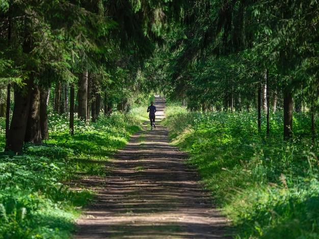 Бегун по тенистой лесной тропинке.