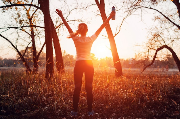 Runner raised arms after workout feeling free and happy succeeded in training, woman admiring sunset,