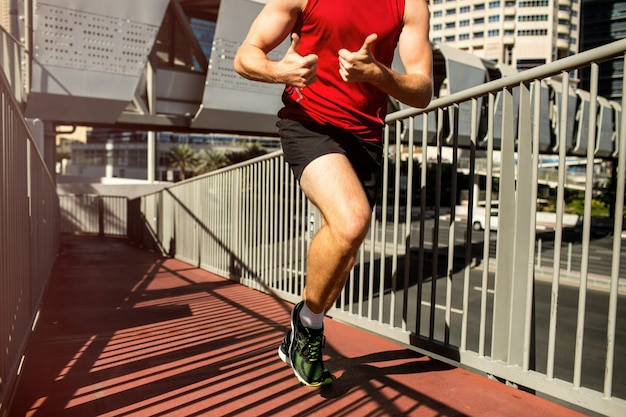 Runner in red t-shirt showes thumbs up in the move