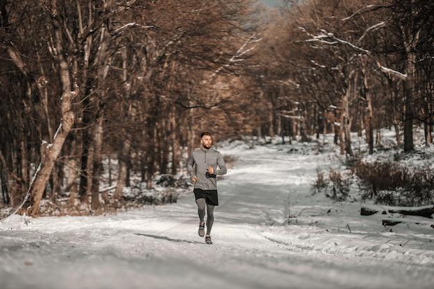 雪の降る冬の日に森を走るランナー。冬のフィットネス、スポーティなライフスタイル、健康的な生活
