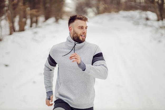 冬の雪の上で自然の中を走るランナー