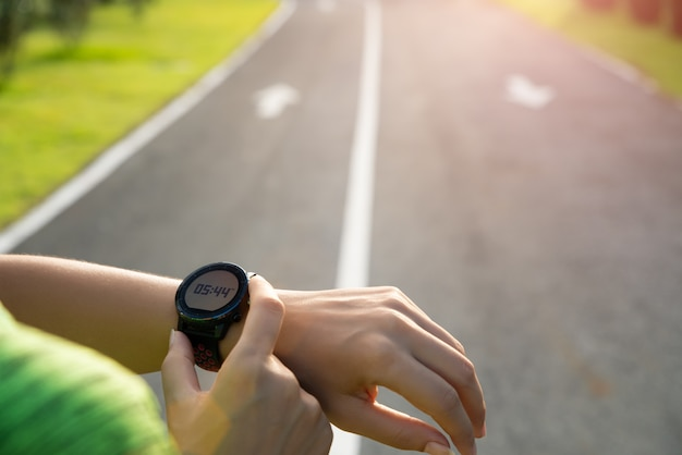 Runner setting up smart watch before training during sunset. exercise.