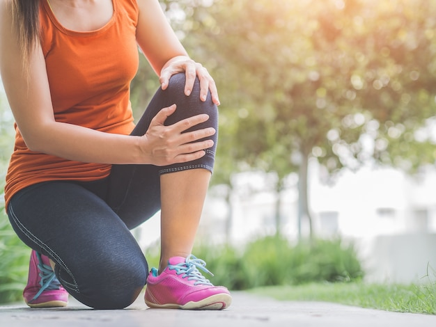 Runner sport knee injury. woman in pain while running in the garden