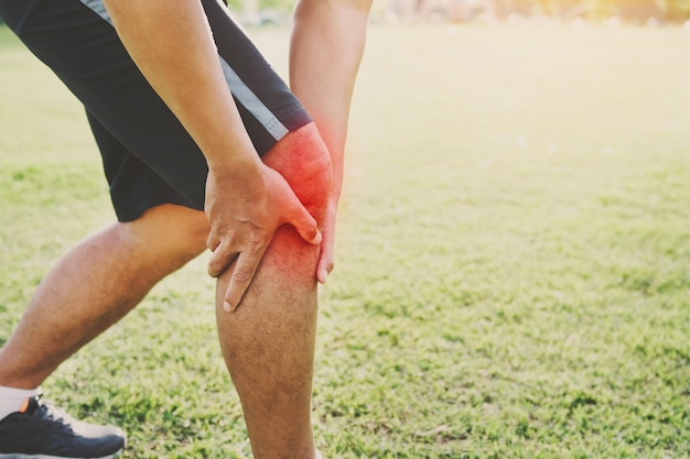 Runner sport with running knee injury at park