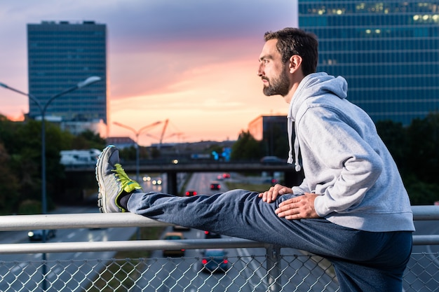 Runner stretching in front of office building at sunset