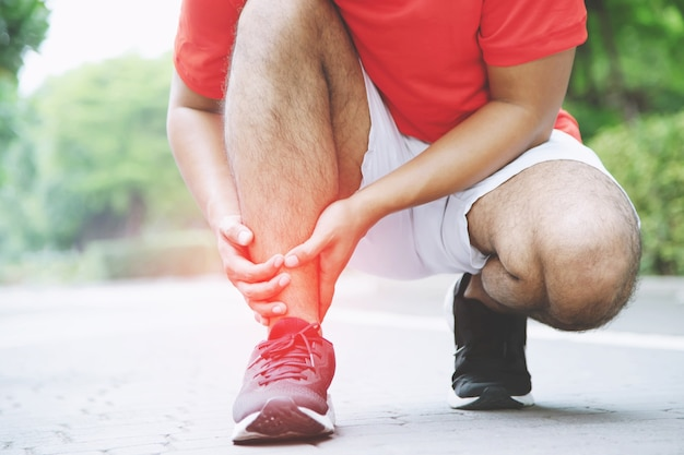 Runner touching painful twisted or broken ankle. athlete runner training accident. sport running ankle sprained sprain cause injury knee. and pain with leg bones.  focus red legs on to show pain.