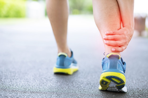 Runner touching painful twisted or broken ankle knee.