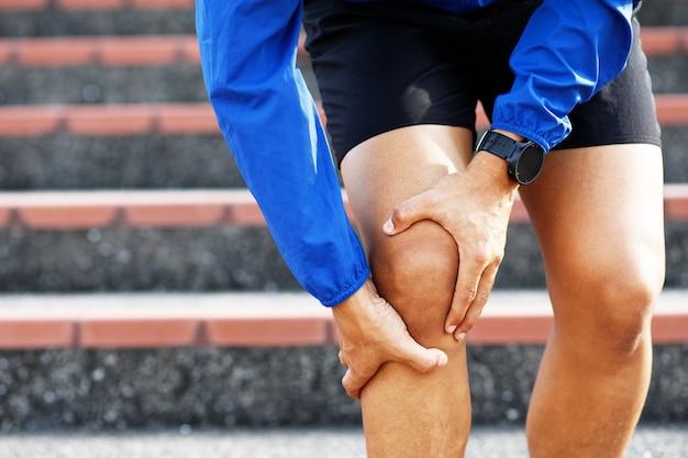 ランナーが痛みを伴うねじれたり壊れたりしている。アスリートのトレーニング、階段の上り下り事故。スポーツ捻挫は膝の怪我を引き起こします。と脚の骨の痛み。
