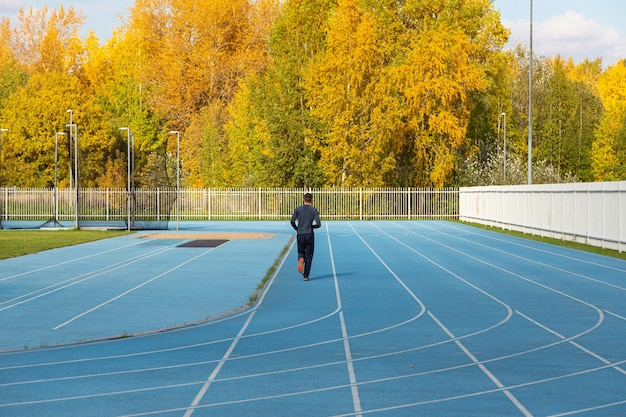 A runner trains on a running track against the background of an autumn forest