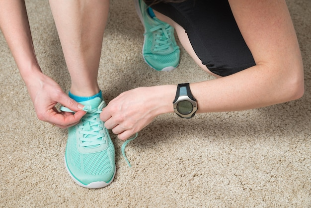 Runner tying laces wearing heat rate monitor and activity tracker for cardio exercise