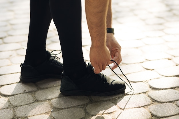 Бегун завязывает шнурки перед тренировкой бегом