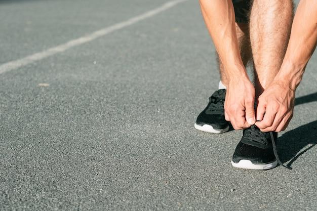 신발 끈을 묶는 러너. 육상 육상. 스포츠와 활동적인 라이프 스타일.
