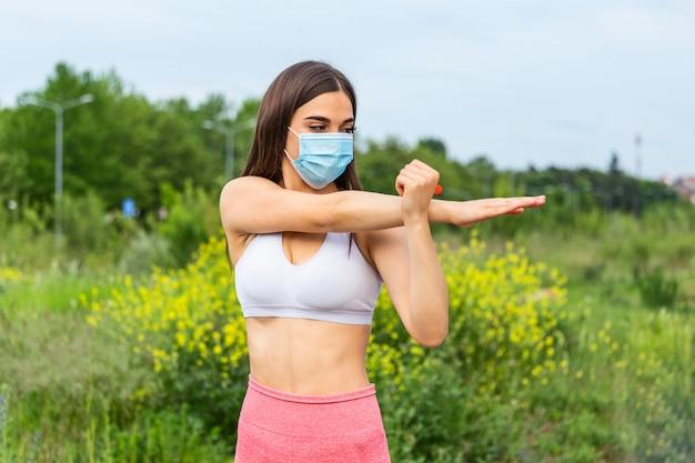 医療用マスク、コロナウイルスパンデミックcovid-19を身に着けているランナー。検疫外科用消毒フェイスマスク保護のアクティブライフ。コロナアウトブレイクでの屋外ランニング。隔離中も体型を保つ