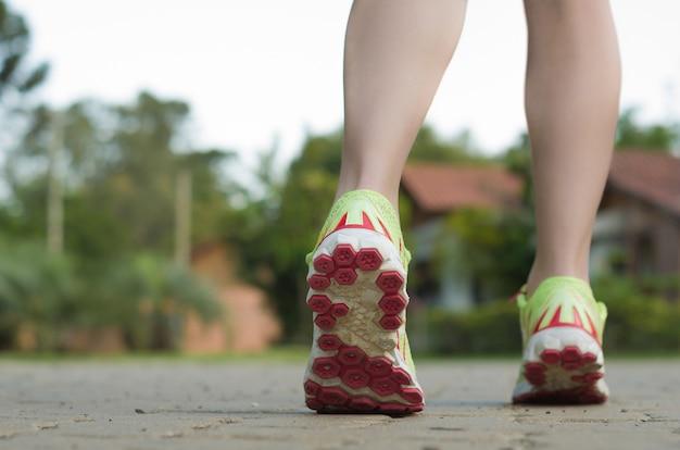 Ноги женщины бегуна бежать на крупном плане дороги на ботинке. разминка jogger спортсмена женского фитнеса в концепции здоровья на восходе солнца. концепция спортивного здорового образа жизни