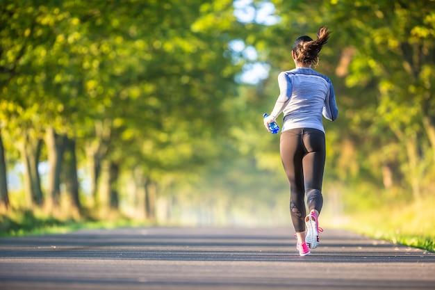 スポーツサーマル下着の秋の公園の木の路地トレーニングのランナーの女性。