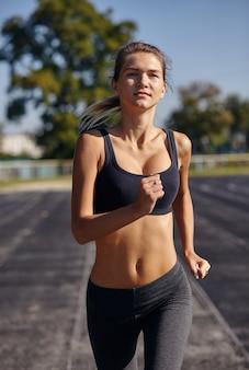 Бегун - женщина, бегущая на открытом воздухе, тренировка для марафонского бега. красивая фитнес-модель за 20.