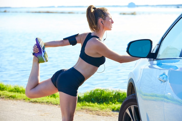 Runner woman stretching on a car in the lake