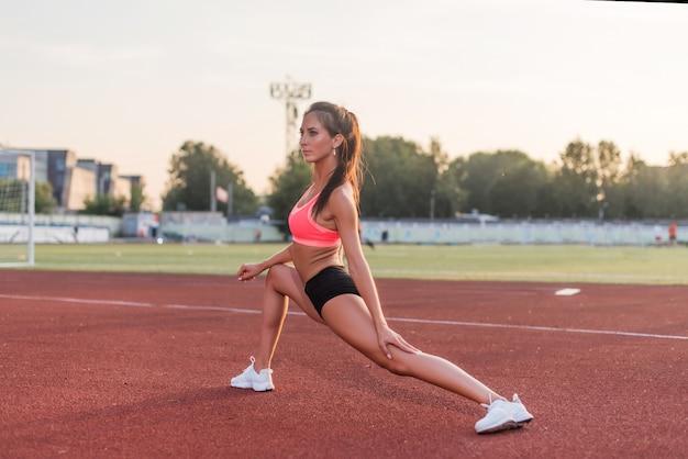 トレーニング前にウォーミングアップ足を伸ばしてランナー女性。