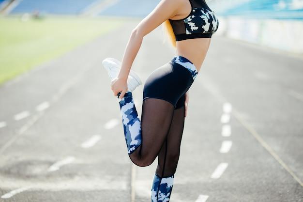 Бегун молодая женщина разминка перед бегом на стадионе трек.