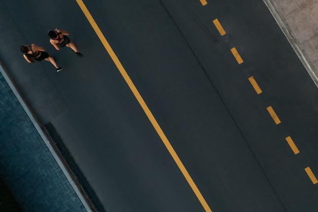 Бегуны бегают люди фитнес. здоровый активный образ жизни. активные девушки бегают вместе на дороге вид сверху. летняя программа тренировок для похудания.