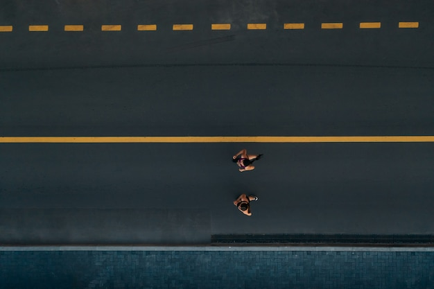 Runners running people fitness. healthy active lifestyle. active girls jogging together on road view from above.