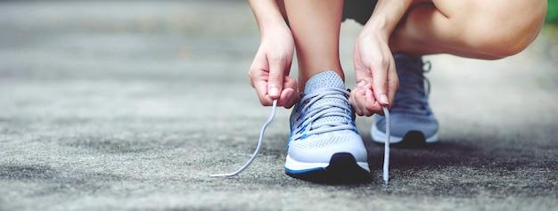 ランナーは公園で靴を結びます。