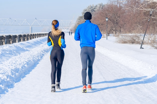 Runners. young running couples. sport man & woman jogging on winter embankment