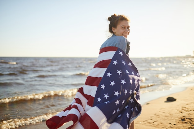 Running along beach with american flag