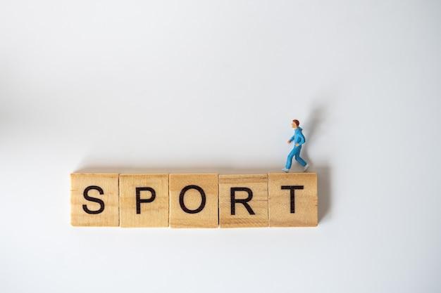 실행 및 피트니스 개념. 러너 미니어처 그림 사람들이 흰색 배경에 나무 편지 블록 문구 스포츠에서 실행합니다.