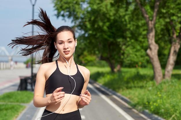 Идущая азиатская женщина на беговой дорожке. утренняя пробежка. тренировка спортсмена