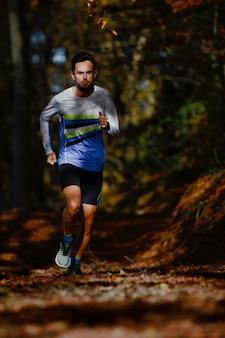 가을 숲에서 마라톤 준비 열차 동안 운동 선수를 실행