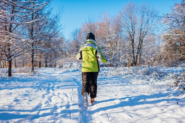 Running athlete woman sprinting in winter forest. training outside in cold snowy weather.