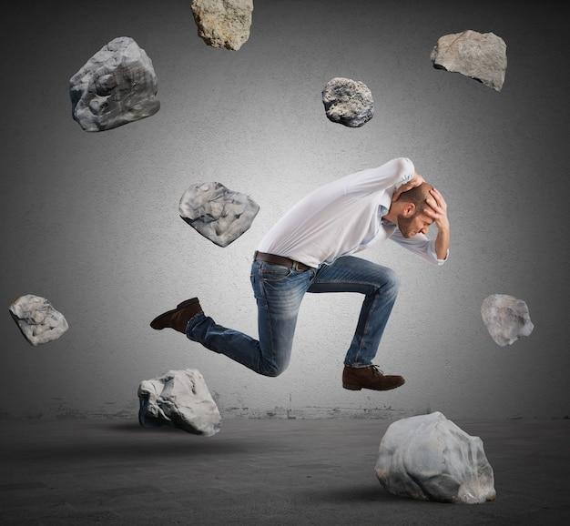 Бегущий бизнесмен спасается от кризиса с помощью каменной бури